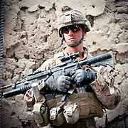 """Location:<br /> Patrol Base Fires, Sangin District, Helmand Province, Afghanistan<br /> <br /> Unit: <br /> 3rd Squad, 1st Platoon, Bravo Company, 1st Battalion, 5th Marines<br /> <br /> Name and Rank: Corporal Michael Minor<br /> <br /> Age: 25<br /> <br /> Hometown: Sea Grove, North Carolina<br /> <br /> Why did you join the Marine Corps?<br /> <br /> """"You can ask my mom, when I was a little kid I always wanted to join the Army or something. I figured if you're gonna join something, why not the hardest?""""<br /> <br /> Describe what it's been like in Sangin so far?<br /> <br /> """"When we first got here nothing really happened, then we started getting shot at a little bit. We took a mass cas July ninth, lost a buddy of mine, Lance Corporal O'Brien. Then three days later we took another mass cas, lost another buddy of mine, Lance Corporal McDaniels, who was our engineer, he was sweeping. Lost a friend of mine, Elliott. He's a machinegunner, lost his leg. Then no more than thirty to forty-five minutes later, we took another mass cas, lost the other engineer, Baucher. Lost the platoon sergeant, lost our CO . . .""""<br /> <br /> What's it like going up against the IED threat?<br /> <br /> """"Well no matter where you go it's always gonna be dangerous if someone's trying to kill you. I mean, here, the biggest threat's IEDs. I mean, getting shot at, hell, these guys aren't marksmen around here. They can shoot at me all day long and I wouldn't give a shit.<br /> <br /> IEDs is a completely different story because they're making 'em out of non-metallic devices and stuff like that, because we have metal detectors that usually picks up the rods and stuff they use in it, but they're using carbon rods from the batteries themselves. What they'll do is throw it in the fire and put a lid over it so that when the battery explodes, the acid doesn't get everywhere. They'll remove the lid then grab the carbon rod, and it's really hard for the metal detector to pick up carbon rods . . .<br />"""