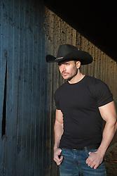 Good Looking cowboy by a rustic barn