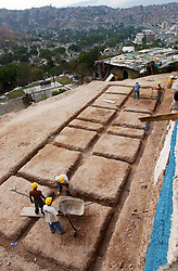 """Three men work on a government project to build houses in """"El Cementerio"""", an area which has one of the many slums in Caracas.  The three, like all the other workers on the project, live in the community.  Many of the houses in the community are currently made of tin and cardboard."""