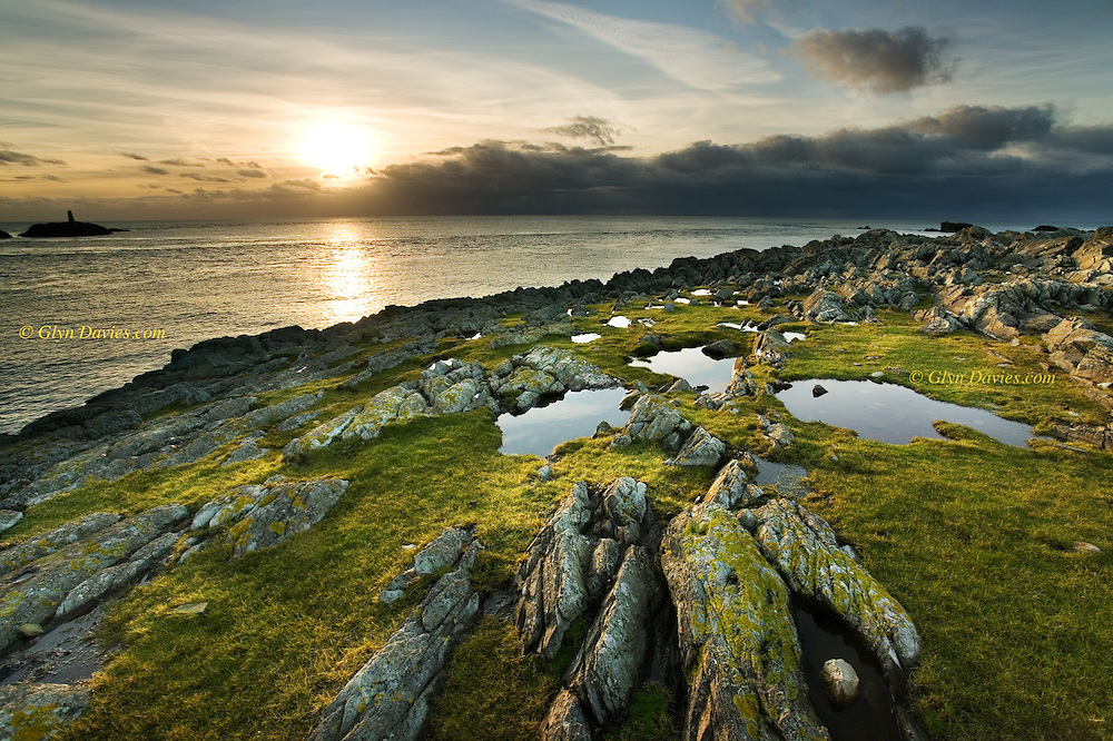 Looking out at an approaching weather front over the Irish Sea at sunset, from the lush green rocky cliff top at Rhoscolyn Head, Holy Island, West Anglesey