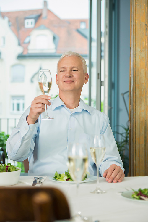 Mature man holding glass of sparkling wine, smiling