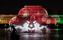 © Licensed to London News Pictures. 21/11/2017. London, UK. Images of snowmen projected onto water vapour in front of the Palm House herald the opening of Christmas at Kew at Royal Botanical Gardens, Kew. The spectacular displays are illuminated by over one million tiny twinkling lights placed all over Kew Gardens - open Wednesdays – Sundays from 22 November 2017 – 2 January 2017. London, UK. Photo credit: Peter Macdiarmid/LNP