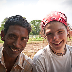 An Italian volunteer and a farm worker rest in the shade.