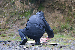 © Licensed to London News Pictures. 11/10/2016. Tintwistle UK. A police forensic's officer removes burnt material from the scene where a murder investigation has started after a badly burnt body was found in a lay-by on the A628 Woodhead Pass near the village of Tintwistle. The body was found by a member of the public & police are working to discover if the victim was male or female. by Photo credit: Andrew McCaren/LNP