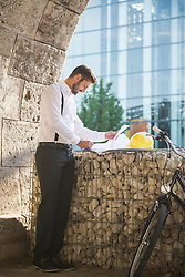 Male architect reading at blueprint at construction site, Munich, Bavaria, Germany