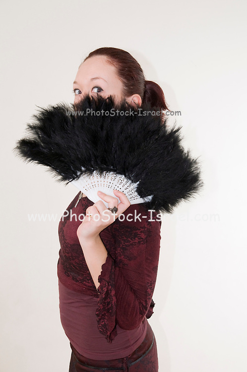 young Gothic teen hiding behind a black feathered fan - Model Release Available