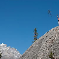 Rock climber Chris Neve throws rappel rope off Rundle Rock near town of Banff in Alberta's Banff National Park, Canada.