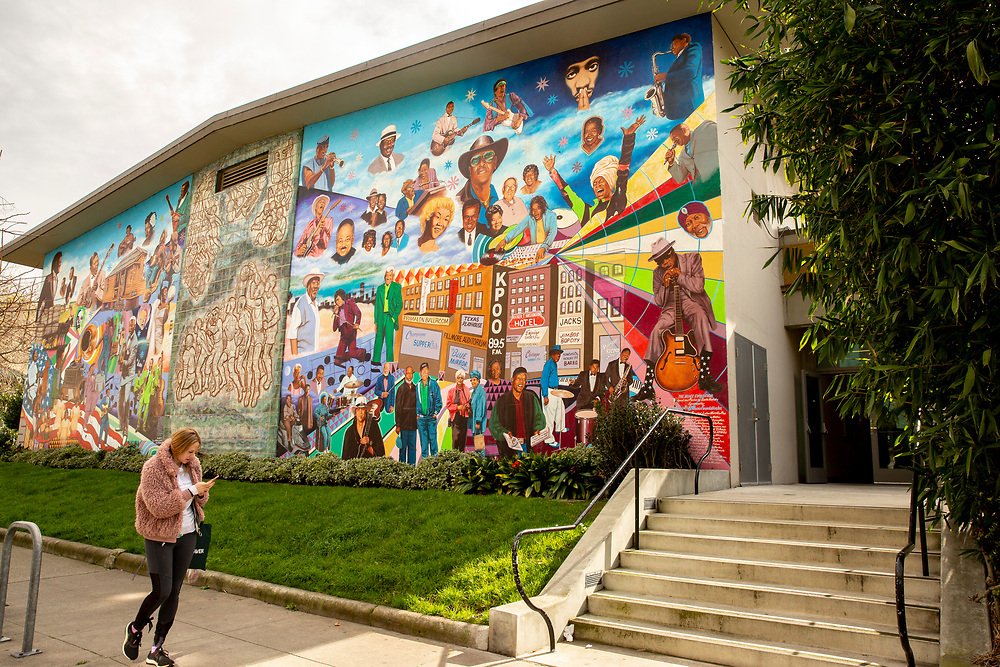 A woman walks past the Fillmore Blues Evolution mural at the Hamilton Recreation Center in the Western Addition neighborhood on Thursday, Feb. 7, 2019, in San Francisco, Calif.