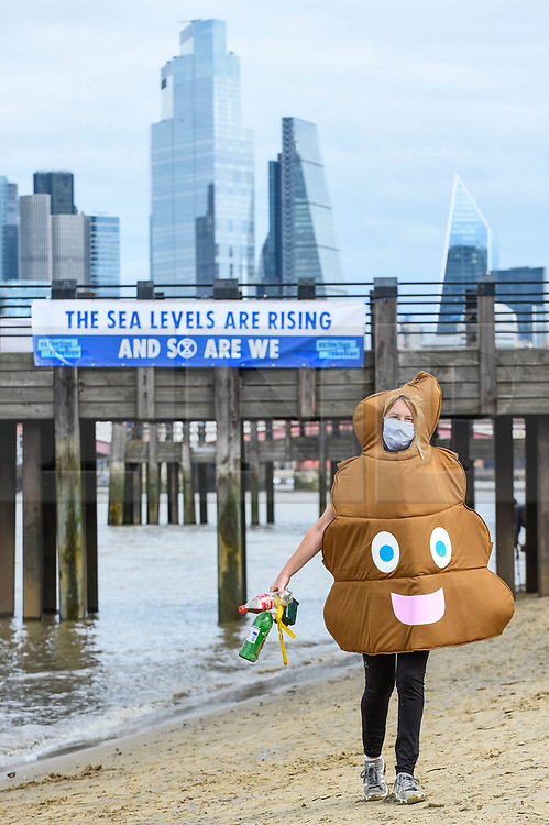 "© Licensed to London News Pictures. 06/09/2020. LONDON, UK.  An activist in fancy dress next to a banner erected by activists from Extinction Rebellion (XR) during a ""Flood Alert"" protest on the shore of the River Thames near Gabriel's Wharf on the South Bank to highlight the effects of climate change on rising sea levels.  Photo credit: Stephen Chung/LNP"