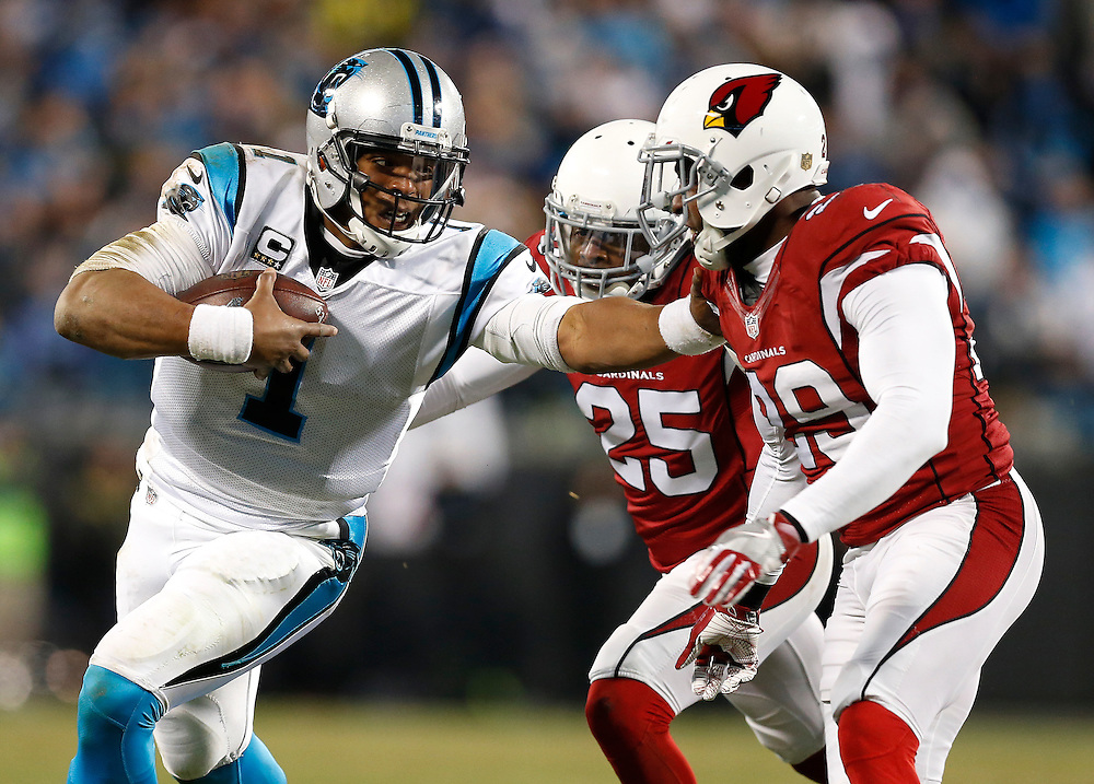 CHARLOTTE, NC - JAN 24:  Quarterback Cam Newton #1 of the Carolina Panthers runs and is pursued by cornerback Jerraud Powers #25 and safety Chris Clemons #29 of the Arizona Cardinals during the NFC Championship game at Bank of America Stadium on January 24, 2016 in Charlotte, North Carolina.