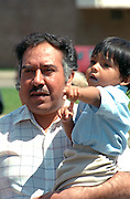 Father holding son ages 54 and 2 at Cinco de Mayo Festival.  St Paul  Minnesota USA