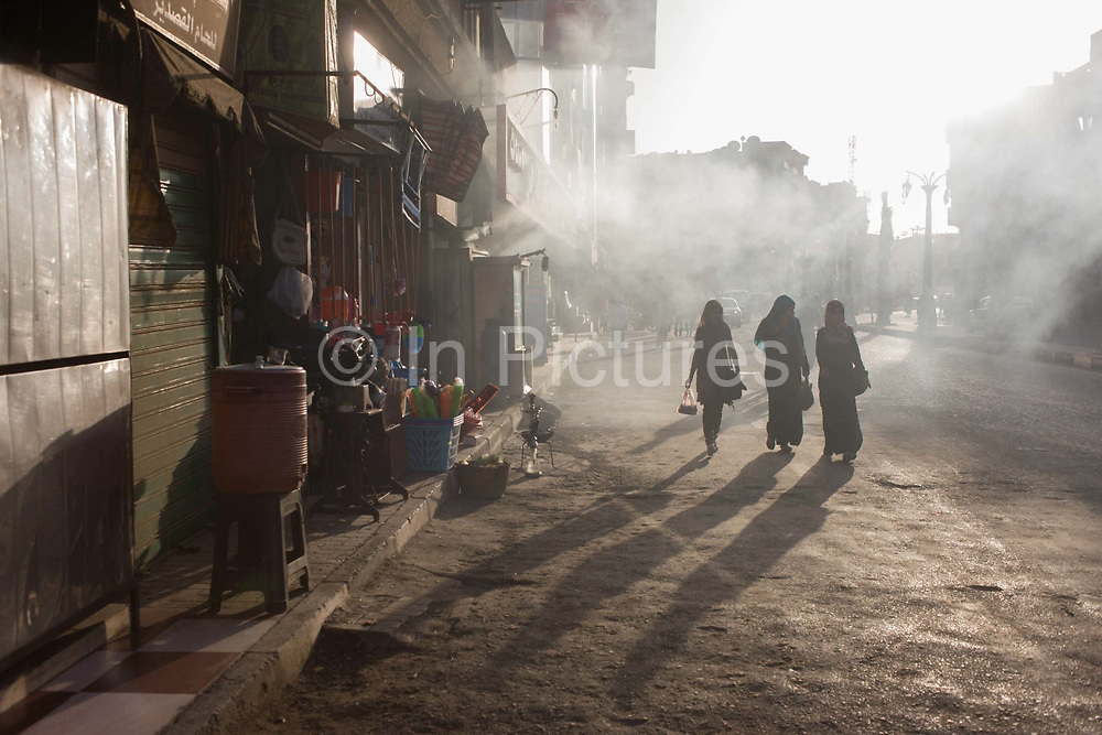Three Egyptian women walk through smoky air, emitted from a kebab business on a street in Luxor, Nile Valley, Egypt. Their shadows fall on the road beyond which is the hooting traffic of the modern Egyptian city, in ancient times called Thebes.