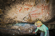 Crouching to make her way below the overhang, an angler skirts a petroglyph where clearly the interpretation of the wall art is that the warrier was proud of his unit.