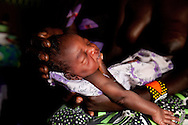 A woman holds her newborn after Todoyoh Martin helped her give birth the night before in her home.