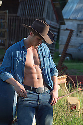 sexy cowboy with an open shirt in a barn on a ranch