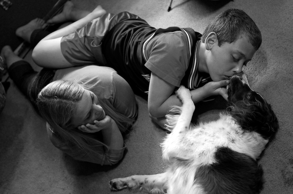 Parker Roos, who suffers from Fragile X, gets a kiss from his dog Daisy as his mother Holly looks on at their home in Canton, Illinois, April 4, 2012.   REUTERS/Jim Young