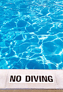 Border of a swimming pool with warning sign that reads No Diving.