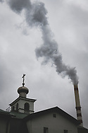 Kohtla-Järve, Estonia - February 22, 2020: A smokestack at the Kohtla-Järve Power Plant is seen across the street from an Orthodox church.