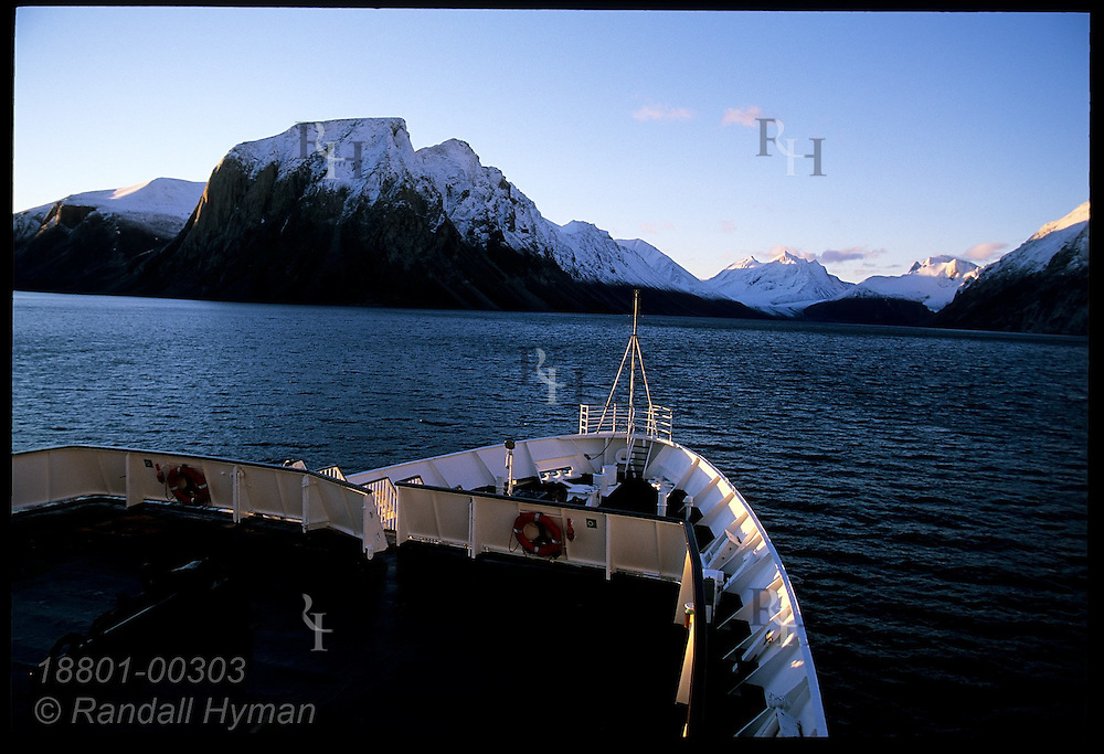 Clipper Adventurer's bow frames snow-capped peaks of Baffin Island at sunrise in early Sept in Dexterity Fjord; Nunavut, Canada