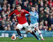 Luke Shaw of Manchester United tackled by Phil Foden of Manchester City during the Premier League match at Old Trafford, Manchester. Picture date: 8th March 2020. Picture credit should read: Darren Staples/Sportimage