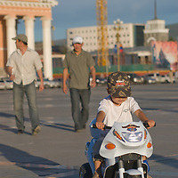 A Mongolian youngster rides his souped-up tricycle in Ulaan Baatar's huge  Sukhbataar Squre.
