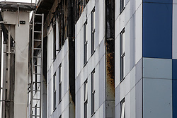 """© Licensed to London News Pictures. 16/11/2019. Bolton, UK. Molten cladding is visible at the site of the blaze . Firefighters work at the scene where a fire broke out overnight (15th/16th November 2019) at a block of flats known as """" The Cube """" , in Bolton Town Centre . At least two people are known to have been treated by paramedics at the scene of the six-story block , which is occupied by students of the University of Bolton . Photo credit: Joel Goodman/LNP"""