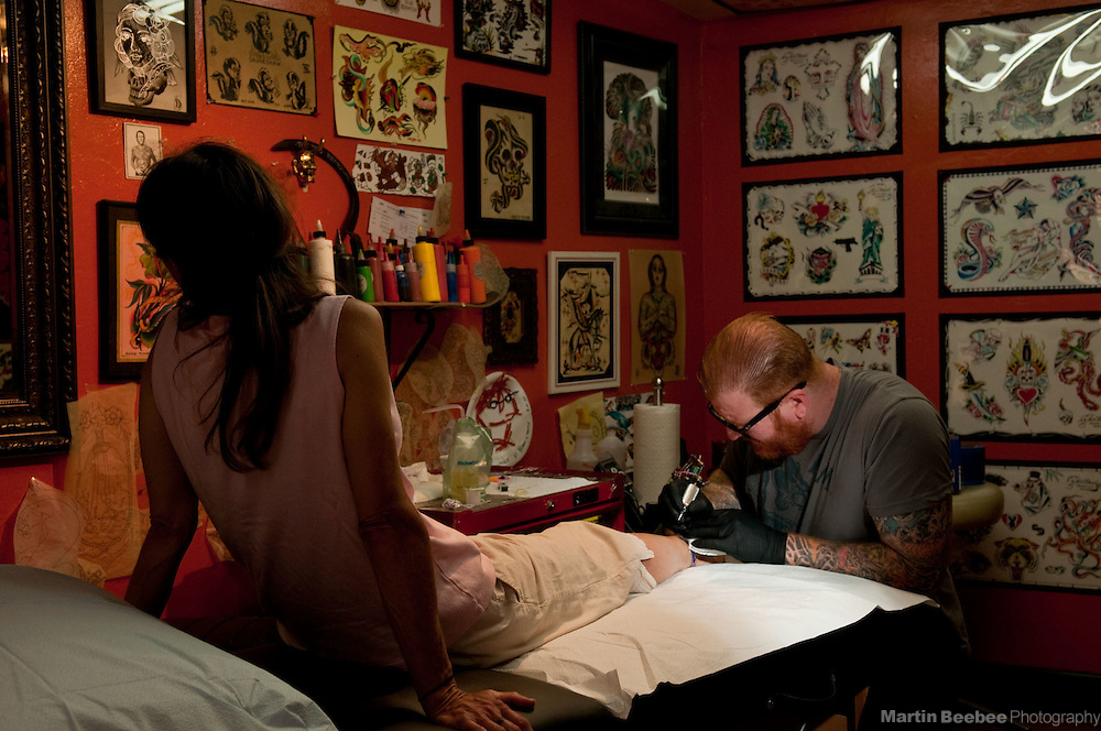 A tattoo artist (Justin Shaw of Faith Tattoo) inks an anklet tattoo for a client