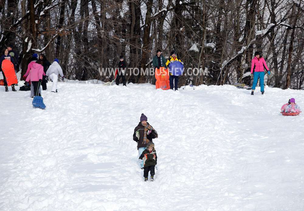 Central Valley, NY - A woman and a young child walk down a hill as other people slide down the hill next to Central Valley Elementary School after a snow storm on  Feb. 27, 2010.
