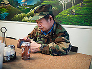 29 FEBRUARY 2020 - ST. PAUL, MINNESOTA: A Hmong man in a cafe in the Hmong Village. Thousands of Hmong people, originally from the mountains of central Laos, settled in the Twin Cities in the late 1970s and early 1980s. Most were refugees displaced by the American war in Southeast Asia. According to the 2010 U.S. Census, there are now 66,000 ethnic Hmong in the Minneapolis-St. Paul area, making it the largest urban Hmong population in the world. Hmong Village, the largest retail and restaurant complex that serves the Hmong community, has more than 250 shops and 17 restaurants.   PHOTO BY JACK KURTZ