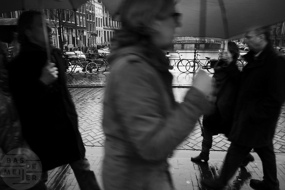 Mensen lopen onder een paraplu door de regen in Amsterdam.<br /> <br /> People are walking under an umbrella in the rain.