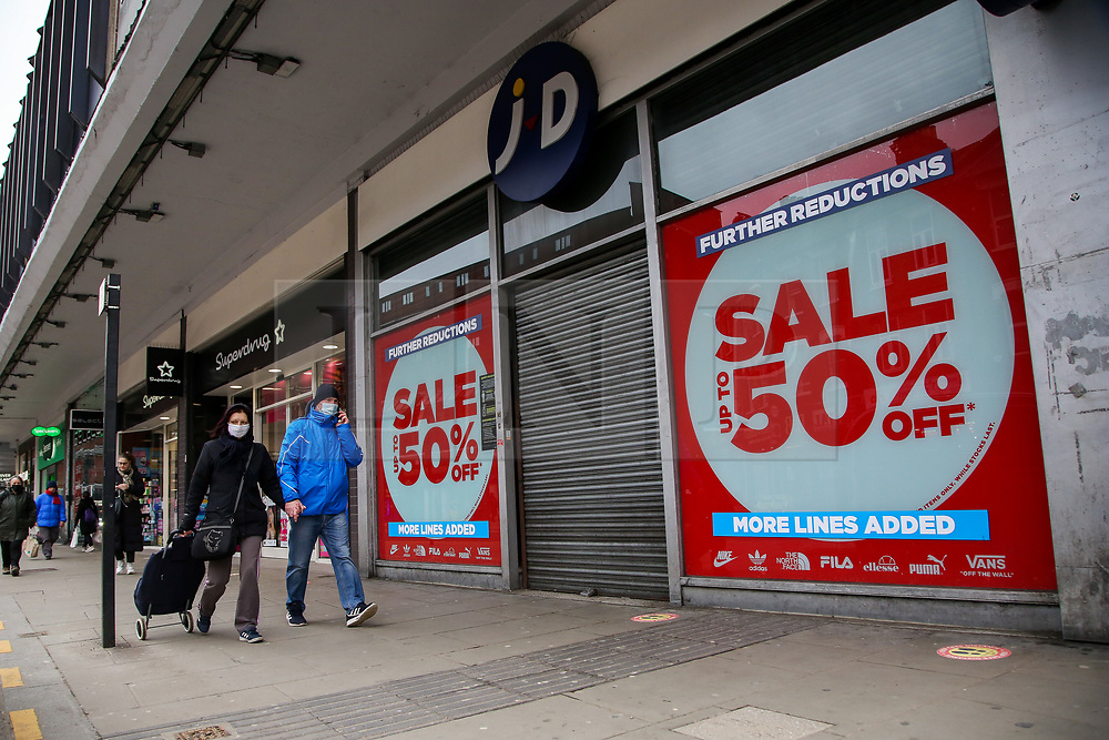 © Licensed to London News Pictures. 19/02/2021. London, UK. Shoppers wearing face coverings walk past closed retail businesses in Wood Green, north London. According to the Office for National Statistics (ONS), in January 2021, retail sales decreased by 8.2%, compared with December 2020. Tighter nationwide coronavirus (COVID-19) restrictions on non-essential retailers which forced them to close led to the drop in January's retail sales. Departmental and clothing store sales were particularly affected. Photo credit: Dinendra Haria/LNP