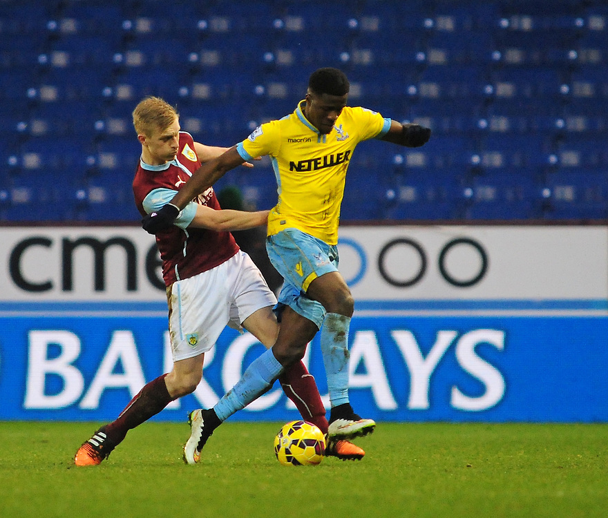 Burnley's Ben Mee vies for possession with Crystal Palace's Wilfried Zaha<br /> <br /> Photographer Chris Vaughan/CameraSport<br /> <br /> Football - Barclays Premiership - Burnley v Crystal Palace - Saturday 17th January 2015 - Turf Moor - Burnley<br /> <br /> © CameraSport - 43 Linden Ave. Countesthorpe. Leicester. England. LE8 5PG - Tel: +44 (0) 116 277 4147 - admin@camerasport.com - www.camerasport.com