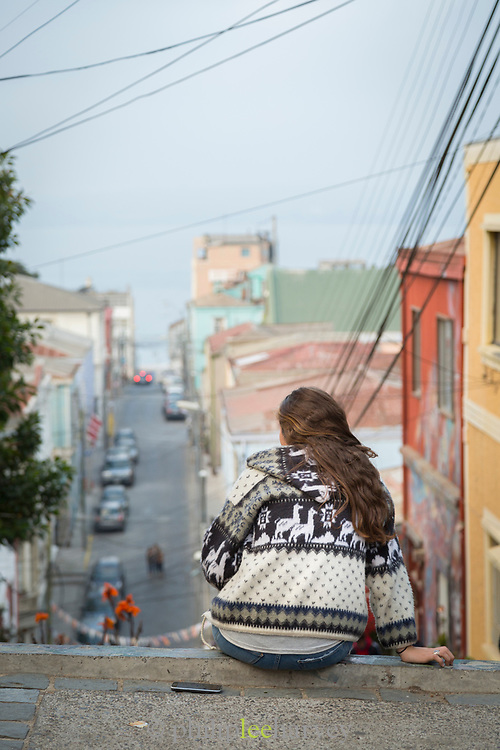 Rear view of woman sitting on steps and looking at view, Valparaiso, Chile
