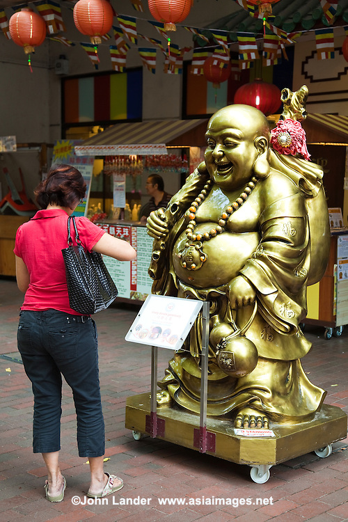 A Singnaporean Chinese woman making a wish to a lucky Buddha in Singapore's Chinatown, making a donation while she's at it.