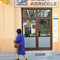 TIMISOARA, ROMANIA - APRIL 21:  A woman walks in front of a branch of Credit Agricole  on April 21, 2013 in Timisoara, Romania.  Romania has abandoned a target deadline of 2015 to switch to the single European currency and will now submit to the European Commission a programme on progress towards the adoption of the Euro, which for the first time will not have a target date. (Photo by Marco Secchi/Getty Images)