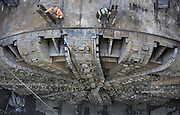 Workers stand on top of the tunnel-boring machine Bertha, looking down at the ring-shaped cutter drive and bearing that has been exposed to be lifted out and repaired.<br />