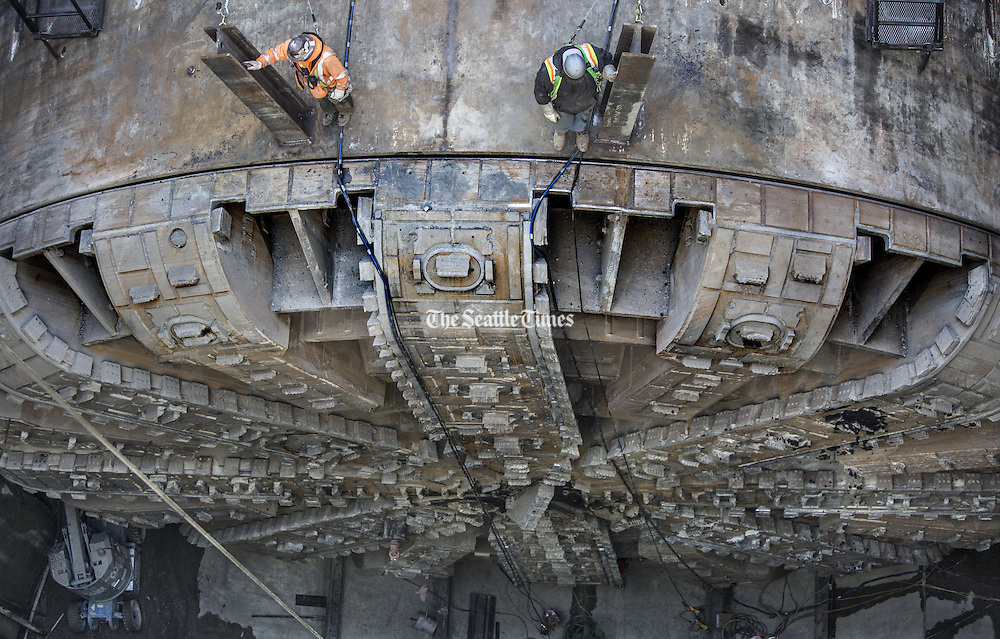Workers stand on top of the tunnel-boring machine Bertha, looking down at the ring-shaped cutter drive and bearing that has been exposed to be lifted out and repaired.<br /> <br /> Steve Ringman / The Seattle Times