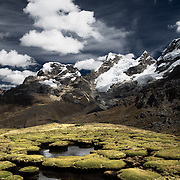 Mountain peaks and what looks like giant moss covered toad stools in a sureal looking landscape located in the Cordillera Huayhuash in the Andes Mountains of Peru.