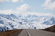 A car drives down the Glenn Highway against a Chugach Mountain backdrop in Alaska.