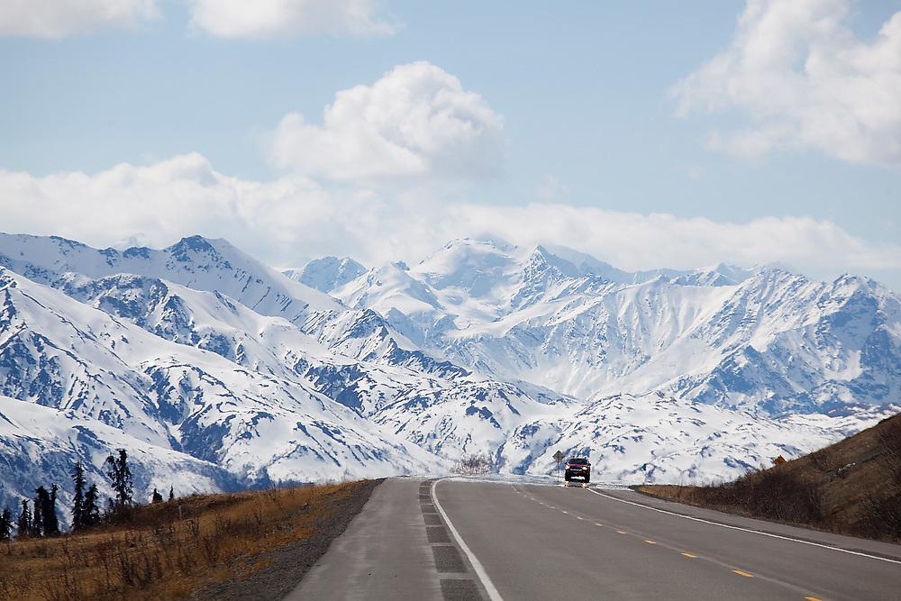A car drives down the Glenn Highway against a Chugach Mountain backdrop in Alaska.