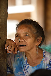 People gather for an Older People's Group meeting where they will discuss individual and group needs.  Pieng 61 years old listens intently <br /> Had Yen Village, Pakseng District, Luang Prabang Province, Lao PDR
