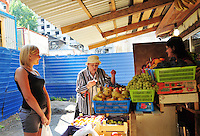 Customers at a tiny but thriving fruit stand sandwiched between new construction and old apartments near the Proletarskaya green line metro stop in St. Petersburg, Russia.