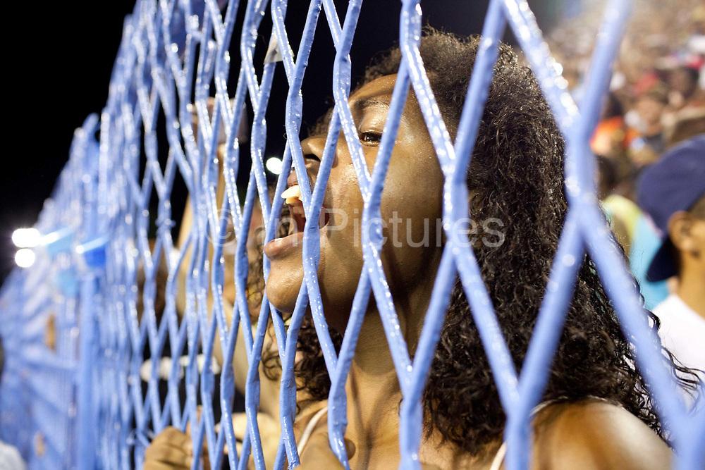 Adoring young girl fan of Salgueiro Samba School shouts appreciation through a fence, before they practice their Carnival procession in the Sambadrome, Rio de Janeiro, Brazil