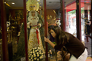 A young Spanish woman and a Virgin Mary mannequin in a shop window during the Semana Santa festivals.