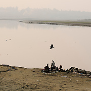 Crow flying over Hindu statues by the Yamuna river