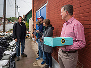 11 MAY 2019 - DAVENPORT, IOWA: JOHN HICKENLOOPER, the former Governor of Colorado, holds a box of donuts while he waits to talk a business owner in a flooded neighborhood of Davenport. Gov. Hickenlooper met with voters in Davenport Saturday. He is campaigning in Iowa this weekend to be the Democratic party's nominee for the US Presidency. Iowa traditionally hosts the the first election event of the presidential selection cycle. The Iowa Caucuses will be on Feb. 3, 2020.          PHOTO BY JACK KURTZ