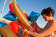 23 SEPTEMBER 2011 - SCOTTSDALE, AZ: Kathy Weltman (CQ), the mother of a cheerleader, brings a balloon bouquet into the stadium before the game at Desert Mountain High School in Scottsdale. Desert Mountain played Notre Dame in Desert Mountain's homecoming football game.    PHOTO BY JACK KURTZ