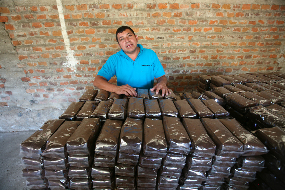 Adilson Barrientos, coffee mill manager at Las Lajas coop, part of UCRAPROBEX, stacking bags of roasted coffee. UCRAPROBEX a certified Fairtrade producer based in El Salvador.
