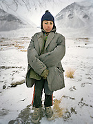 Young Wakhi with his father's suit for warmth..Wakhis outside in Sarhad, the first village coming down from the Little Pamir. .Winter expedition through the Wakhan Corridor and into the Afghan Pamir mountains, to document the life of the Afghan Kyrgyz tribe. January/February 2008. Afghanistan