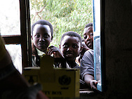 Rwanda- Curious teenage girls watch as a woman has a blood test to check for      HIV infection during a campaign at the Gary Scheer school in Rwanda's South Province in February 2008.
